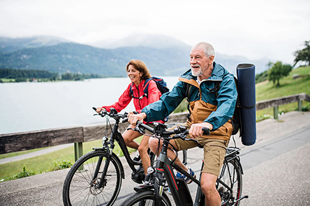 senior-couple-tourist-with-bicycles-cycling-on-road